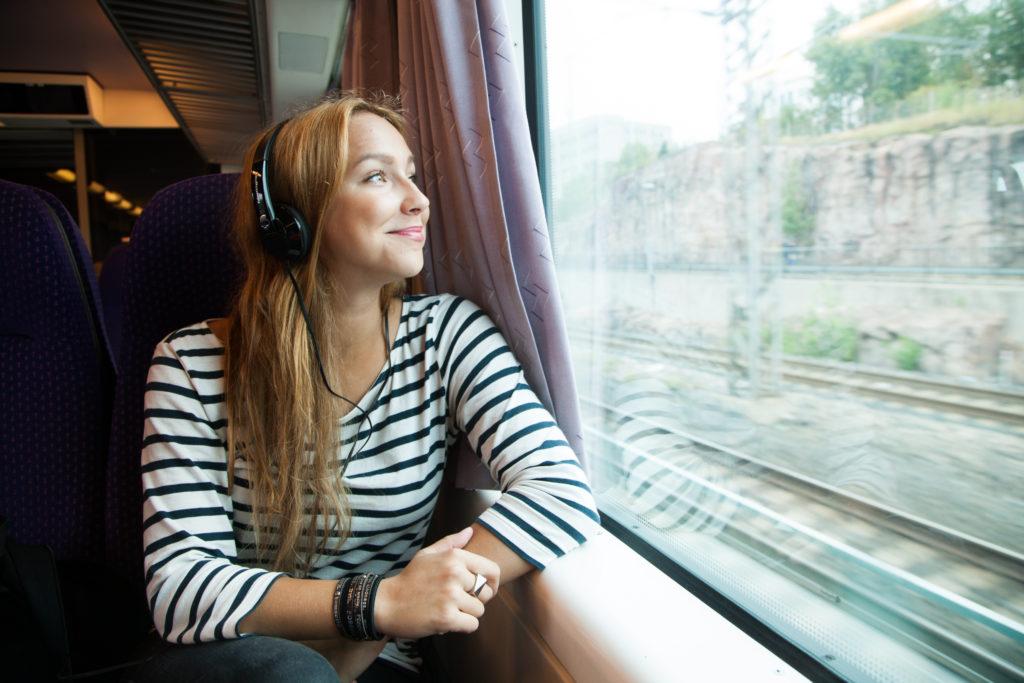 Nainen istuu junassa kuulokkeet korvillaan.