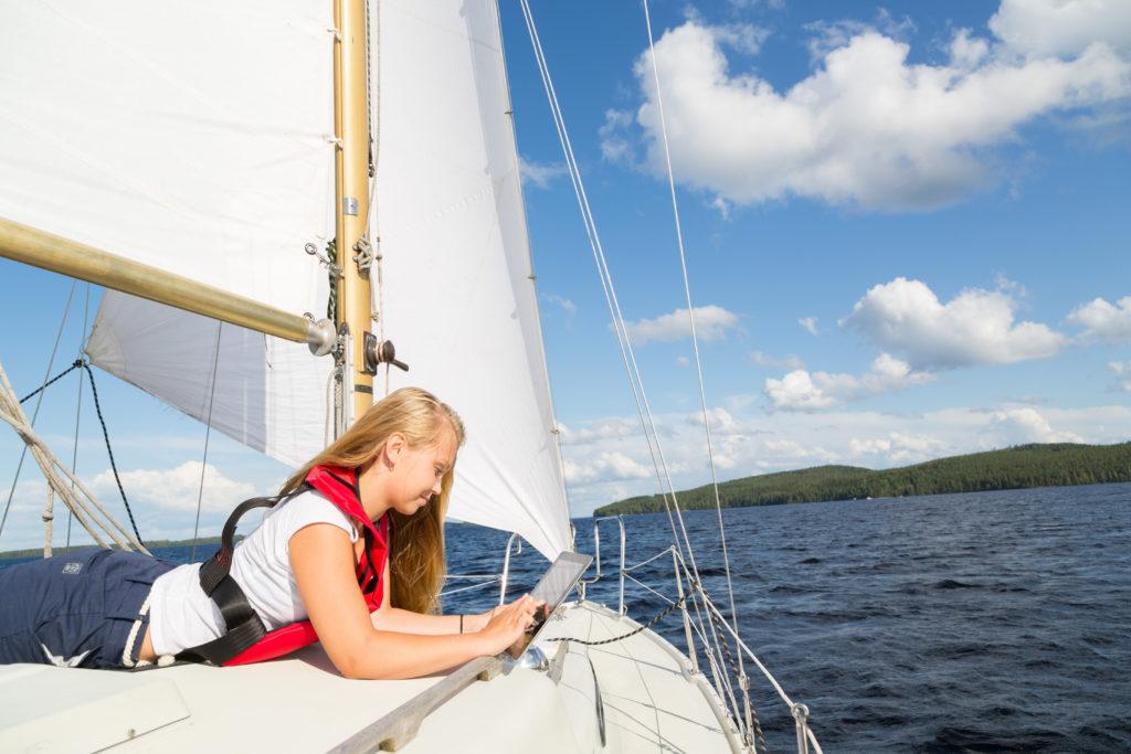 tyttö lukee pädiä purjelaivan kannella