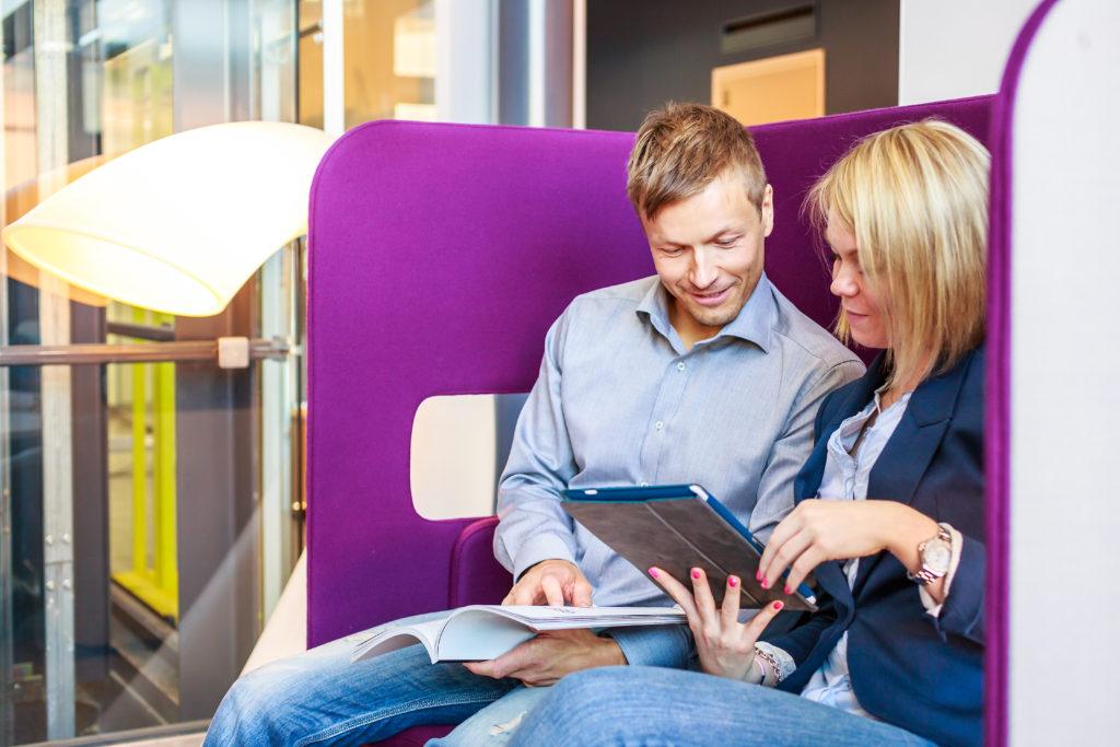 nainen ja mies toimistossa, tutkivat tietokonetta.